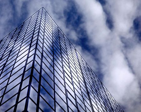 Glass windowed urban office sky scrapers abstract with blue sky and clouds photo