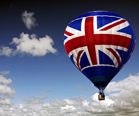 Colouful rood wit en blauw hete lucht ballon stijgt in een bewolkte hemel  Stockfoto