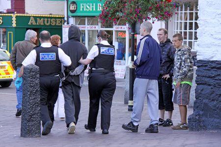 mujer policia: Brixham, Devon, GB, 29 de agosto de 2009 polic�a brit�nica de arrestar a un criminal masculino