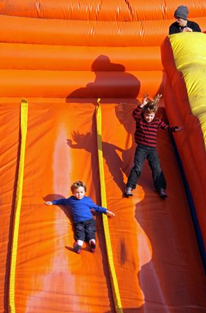 bounce: Tulleys Farm, Crawley, UK, 291009 children on a large orange inflatable slide at a halloween festival