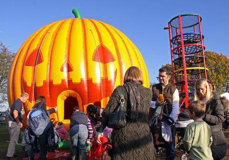 Tulleys Farm, Crawley, UK, 291009 Children and parents having fun with a halloween pumpkin bouncy castle