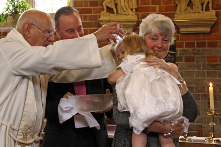 Goring, Berkshire, UK, 25th October 2009, a priest  vicar doing the christening service of a baby girl Editorial