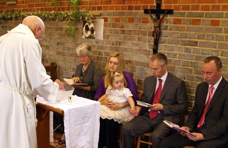catholism: Goring, Berkshire, UK, 25th October 2009, a priest  vicar doing a childs christening service