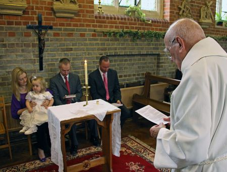 vicar: Goring, Berkshire, UK, 25th October 2009, a priest  vicar doing the christening service of a baby girl Editorial