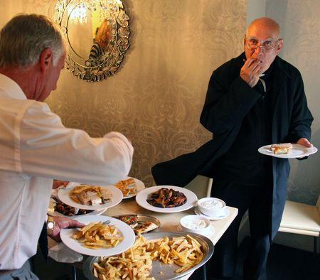 catholism: Goring, Berkshire, UK, 25th October 2009, a priest  vicar enjoying food after a christening