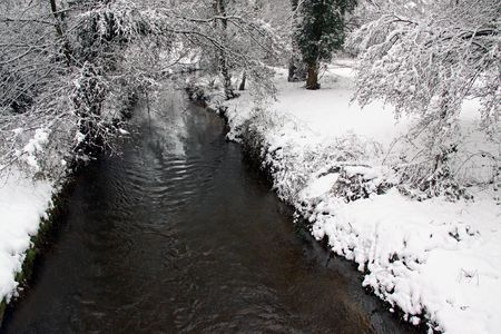 Rural countryside scene of a river / stream in winter snow through woodland trees Stock Photo - 6408780