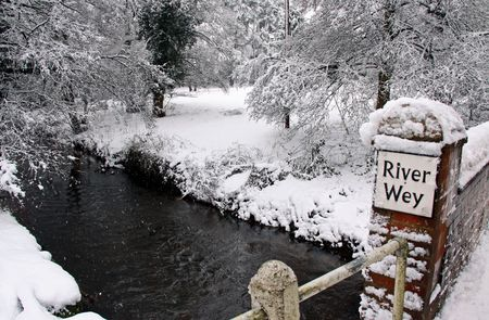 Rural countryside scene of a bridged stream in winter snow through woodland trees Stock Photo - 6408774