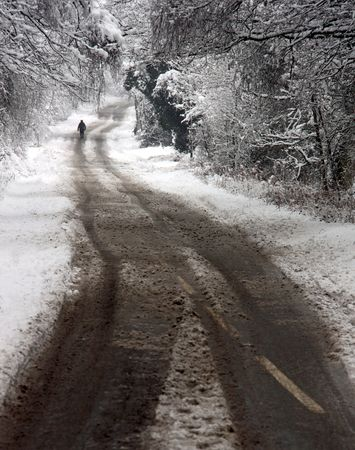 A man walking down a winter snow covered road through rural forest trees and woodland countryside photo
