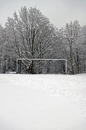 Winter scene of soccer goalposts standing in a snow covered football pitch with trees and woodland countryside background
