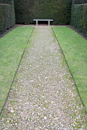 A pathway leading to a garden bench photo