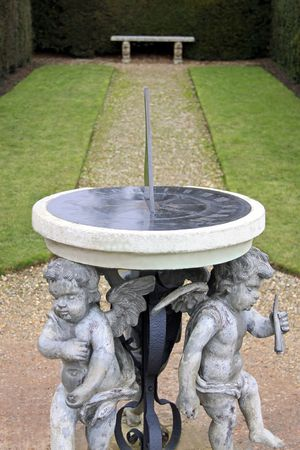 An antique cherub sun dial timepiece in a garden with stone bench and pathway photo