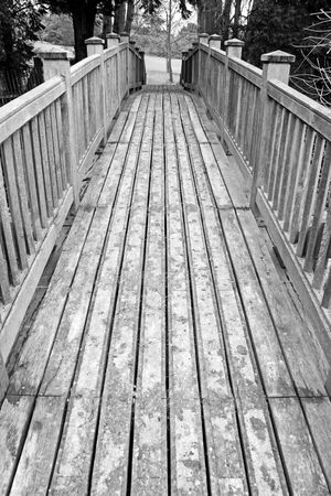 bridged: A wooden bridge crossing over into rural countryside Stock Photo
