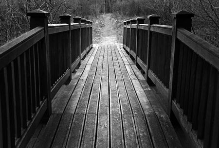 A wooden bridge crossing over into rural countryside Imagens