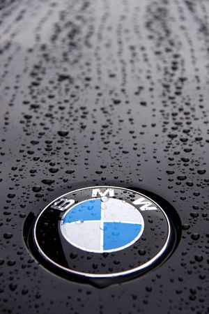 Bonnet and badge of a black BMW 1 Series with rain drops Editorial