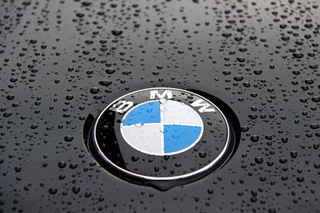 engine bonnet: Bonnet and badge of a black BMW 1 Series with rain drops Editorial
