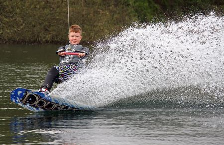 Heron Lake, Wraysbury, UK April 25th 2010: a young boy wakeboarding  surfing at the British Disabled Water Ski-ing Association BDWSA
