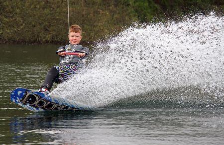 Heron Lake, Wraysbury, UK April 25th 2010: a young boy wakeboarding  surfing at the British Disabled Water Ski-ing Association BDWSA