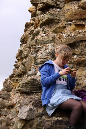 hastings: Hastings UK, May 3rd 2010, a girl sitting on Hastings Castle ruins at Jack In The Green Festival, May Day Weekend