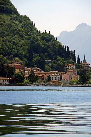 View of tree covered mountains and town at Lake Como in Italy photo