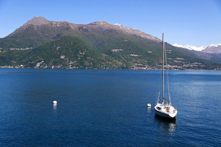 treviso: A sailing yacht on Lake Como, Italy with Treviso mountains
