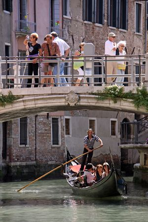 Venice, Italy, 21510 Italian gondolier and tourists in a gondola and on a bridge over a Venice waterway