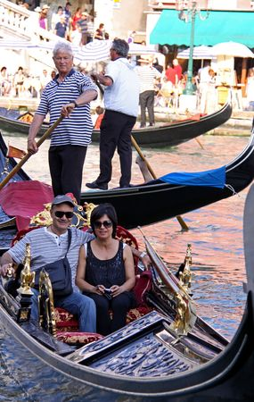 Venice, Italy, 21510 Italian gondoliers and tourists in gondolas next to the Rialto Bridge on the Grand Canal
