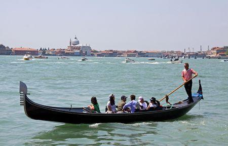 Venice, Italy, 21510 Italian gondolier and tourists in a gondola near Saint Marks Square