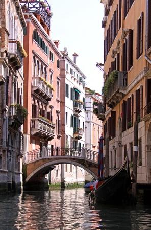 An Italian gondola boat and bridge over a canal in Venice , Italy photo