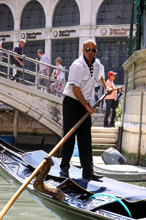 Venice, Italy, 21510 Italian gondolier and tourist passengers in a gondola in a Venetian canal