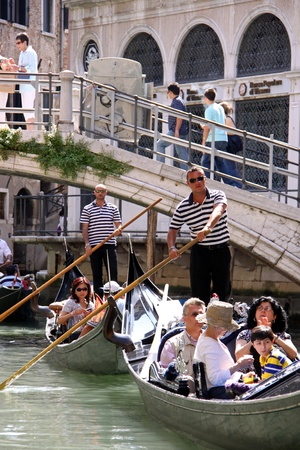 Venice, Italy, 21/5/10 Italian gondoliers and tourist passengers in gondolas on a Venetian canal Stock Photo - 9472225
