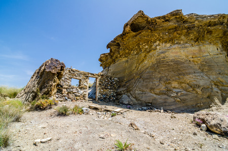 hause: There are a lot of abandoned movie sets in the desert of Tabernas. This is one of them. Is only the front of a house, made of stones, between a big rock and another smaller, working as walls.