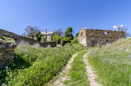 Dirt road and ruins of houses Stock Photo