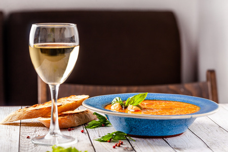 Italian European Cuisine. Spicy fish soup from seafood, salmon and trout, with vegetables in a blue plate. on the table in the restaurant is a glass of white wine. Copy space, selective focus Stock Photo