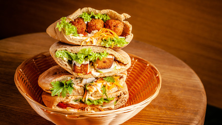 Concept of vegetarian food. pita with falafel, salad, vegetables, tofu cheese in a wicker basket on a wooden table. background image. Copy space, selective focus