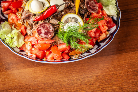 Traditional Uzbek oriental cuisine. Samarkand pilaf from mutton with vegetables, to a company of several people in a restaurant. background image. Copy space, selective focus