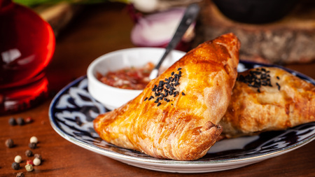 Uzbek samsa in national plate with tomato sauce on a wooden table. end of the eastern baking.