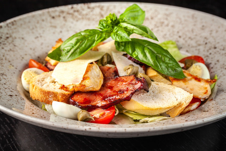 Italian Cuisine. Classic Caesar salad with chicken, cherry tomatoes, mix salad, parmesan cheese, bread croutons, rusks and basil. The concept is a beautiful serve in the restaurant. Copy space