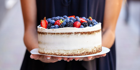 The girl is holding a cake with forest berries, strawberries, blueberries, on the street in the city. A concept for the production of cakes, bakeries, restaurants. Background image 免版税图像