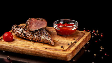 two juicy beef pepper steak with a air fryer medium rare, with a red sharp sauce on a wooden board, on a black background. Copy space