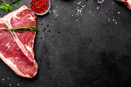 Meat raw steaks lie on a black background with vegetables, tomatoes, marasmade, mushrooms. background image. side view, copy space, top view