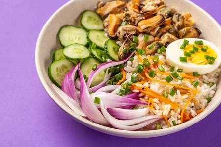 Hawaiian Pake salad with mussels, boiled egg, red onion, cucumber and rice, with black sesame. in a gray plate. On a purple colored trendy background in 2018. copy space, top view