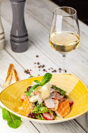 Caesar salad with salmon. mix of salads, cherry tomatoes, parmesan cheese, basil. A dish in a ceramic plate is on a wooden table in a restaurant. A glass of white wine is on the table. selective focus Imagens