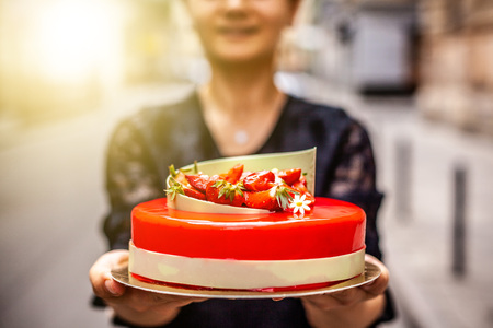 The girl on the street in her hands holds a cake of mousse, covered with a mirror glaze, on top of the cake the decor of strawberries, raspberries and white chocolate.