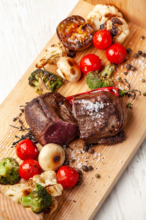 Two juicy steaks with roast medium rare, with grilled vegetables on a wooden board. Cooked with air fryers. A laid table in the restaurant for a holiday or birthday, evening dinner. selective focus Stock Photo