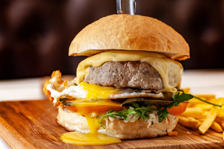 Concept of street food. American burger with a juicy meat patty, salad, tomato and poached egg, with a knife for a burger. Copy space