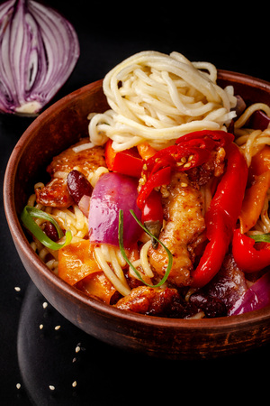 Japanese, Chinese udon noodles with chicken and vegetables, Bulgarian pepper, red onion, white and black sesame. dish in a ceramic dish made of red clay on a black background. Stock fotó