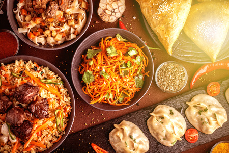 Assorted Uzbek food set, pilaf, samsa, lagman, manta and Korean carrots, Uzbek restaurant concept, Uzbek food feast. Festive, homemade lunch, dinner for the whole family. copy space, top view Banque d'images