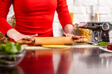 Step by step. Manual process of making Italian pasta Fettuccine. Home pasta with Pasta Maker. Flour, semola di grano duro, eggs, tomatoes, basil lie on a wooden table. For the recipe.