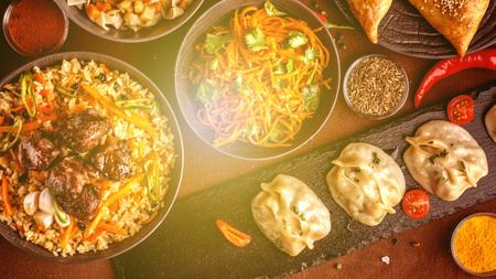 Assortiment de plats ouzbeks, pilaf, samsa, lagman, manta et carottes coréennes, concept de restaurant ouzbek, festin culinaire ouzbek. Déjeuner festif fait maison, dîner pour toute la famille. espace de copie, vue de dessus