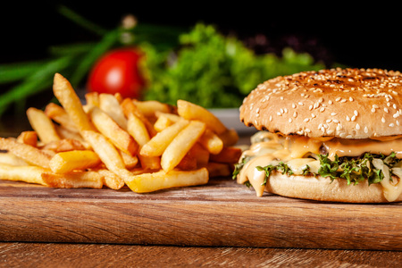 The concept of American cuisine. Juicy burger with meat patty, with cheese and french fries lying on a wooden board in a restaurant. Near a glass of beer with foam. Stockfoto